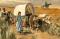 woman walking beside a wagon