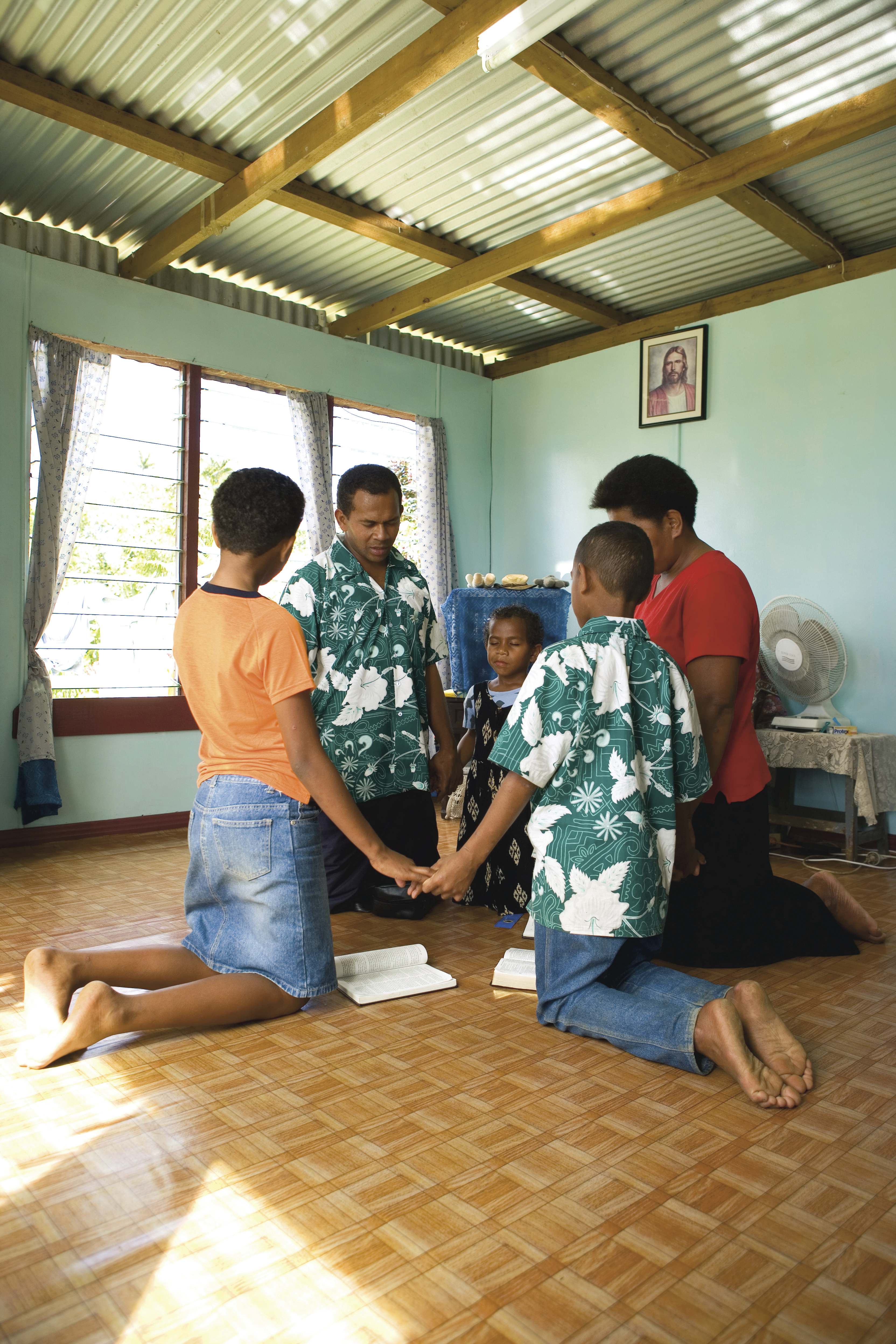 A family in Fiji holding hands and praying together.