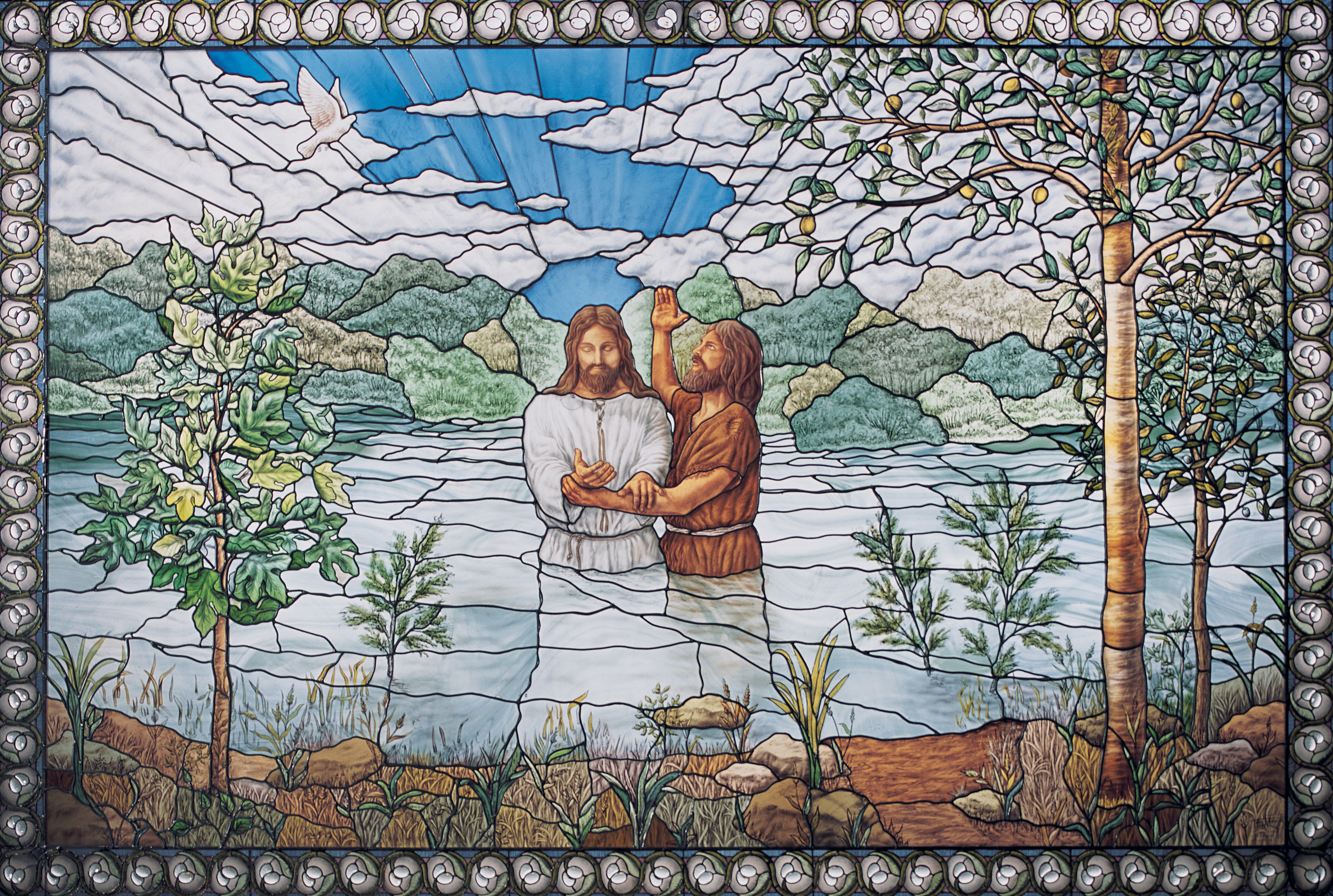A stained glass window depicting Jesus Christ being baptized by John the Baptist.