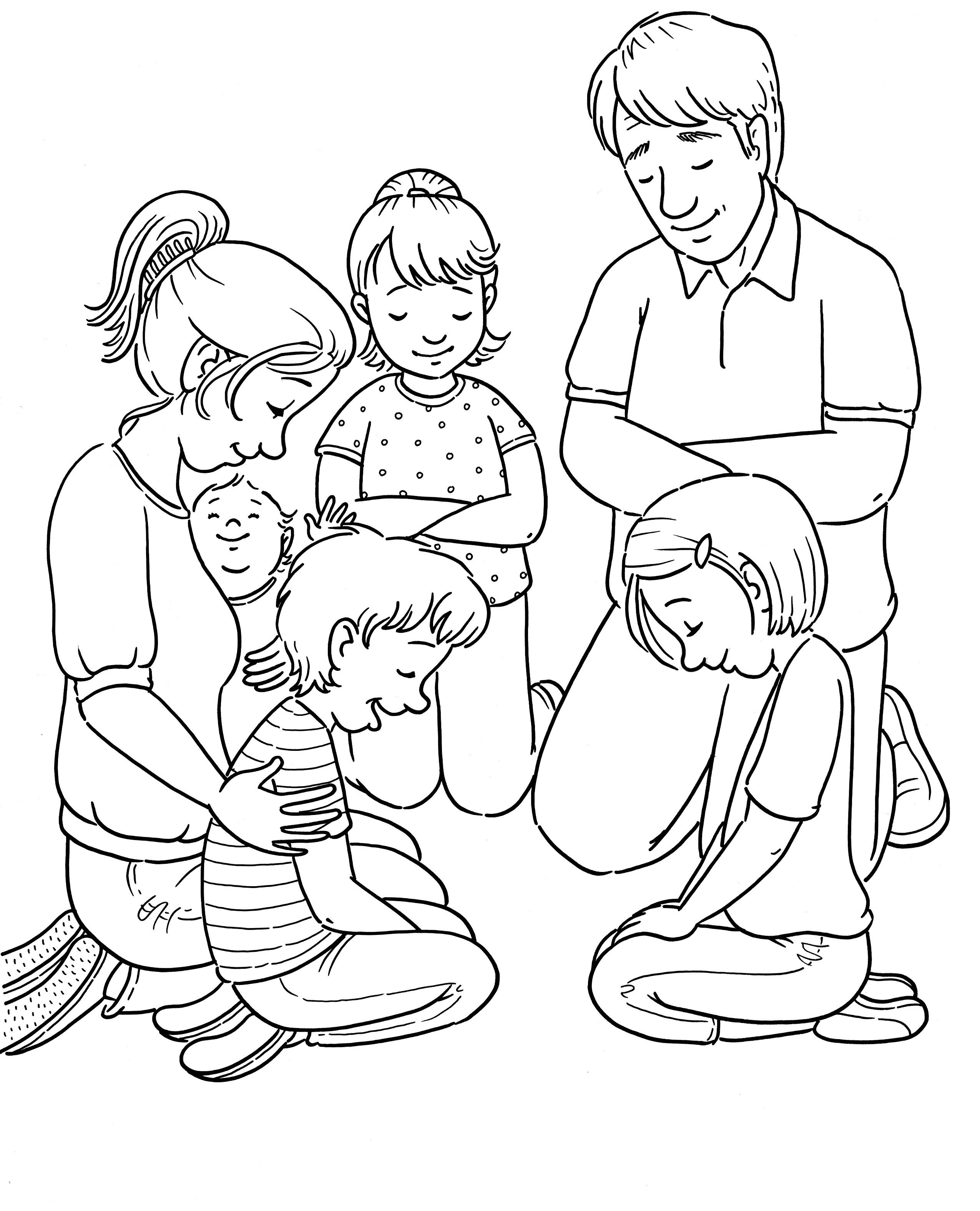 A family kneels in a circle and prays together.