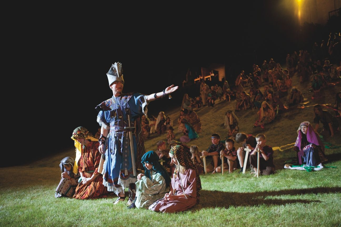 One Nephite standing with an outstretched arm in front of many Nephite children sitting down at the Manti Pageant.
