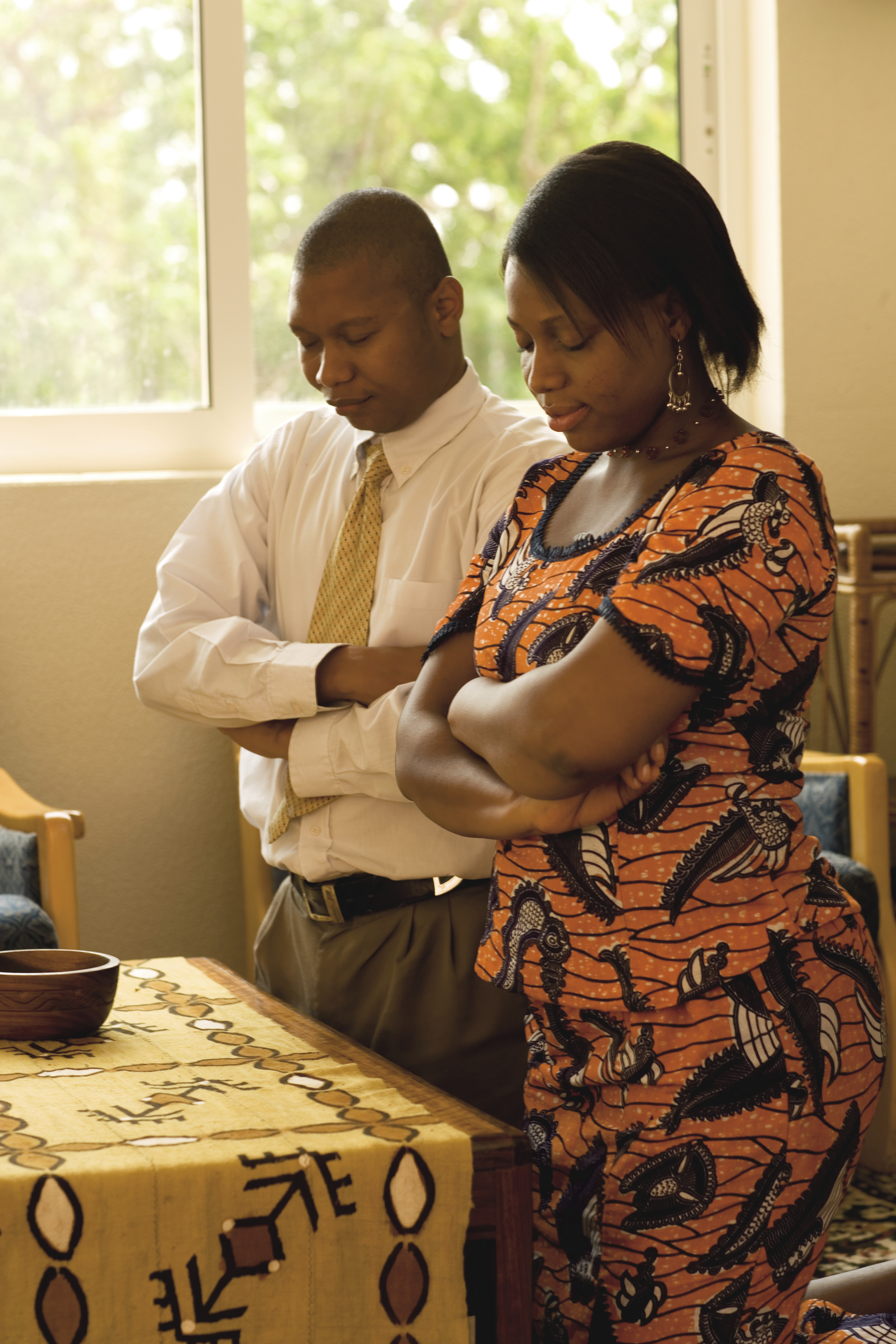 A husband and wife from Ghana kneeling in prayer together.