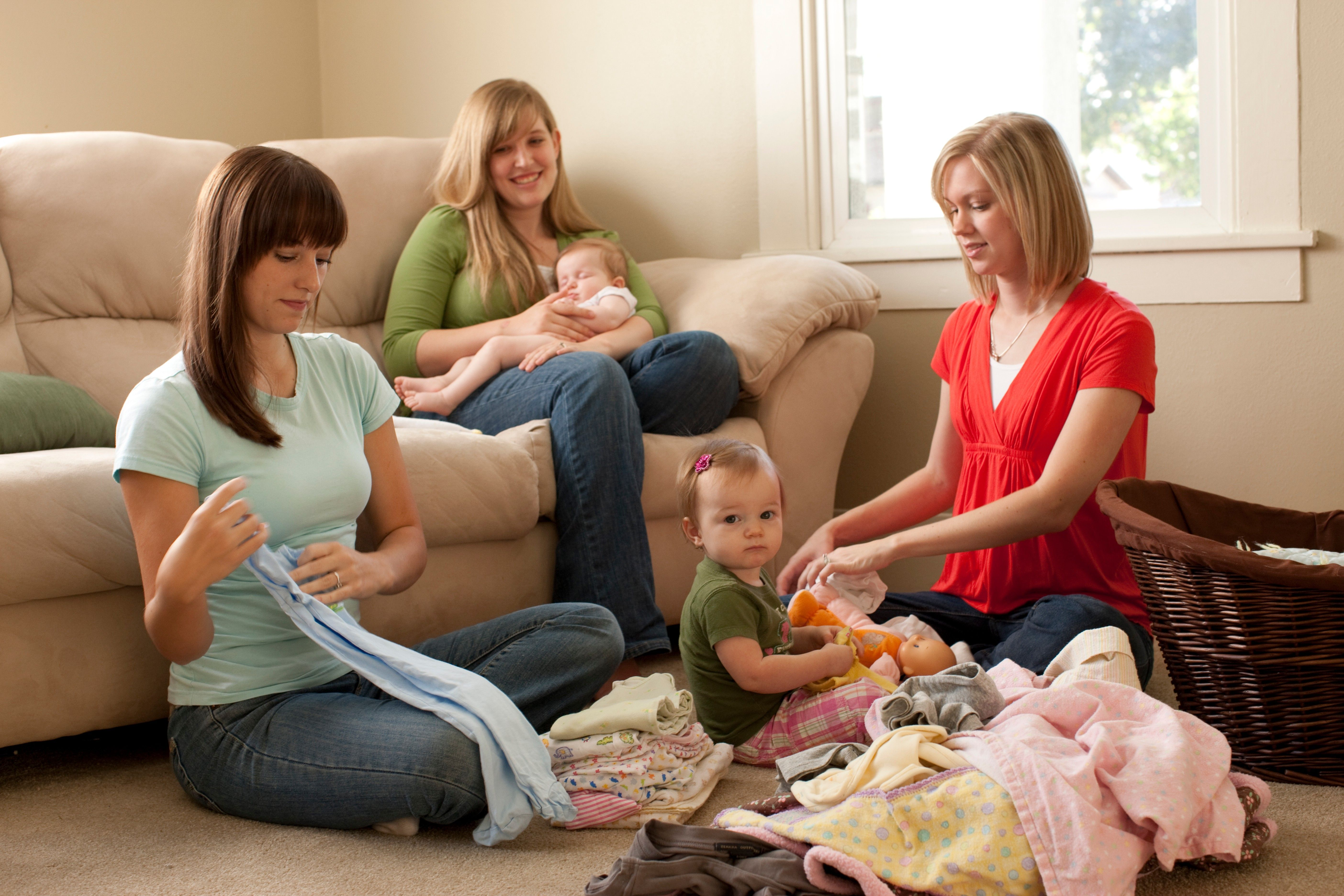 Ministering sisters help a woman with two children fold her laundry.