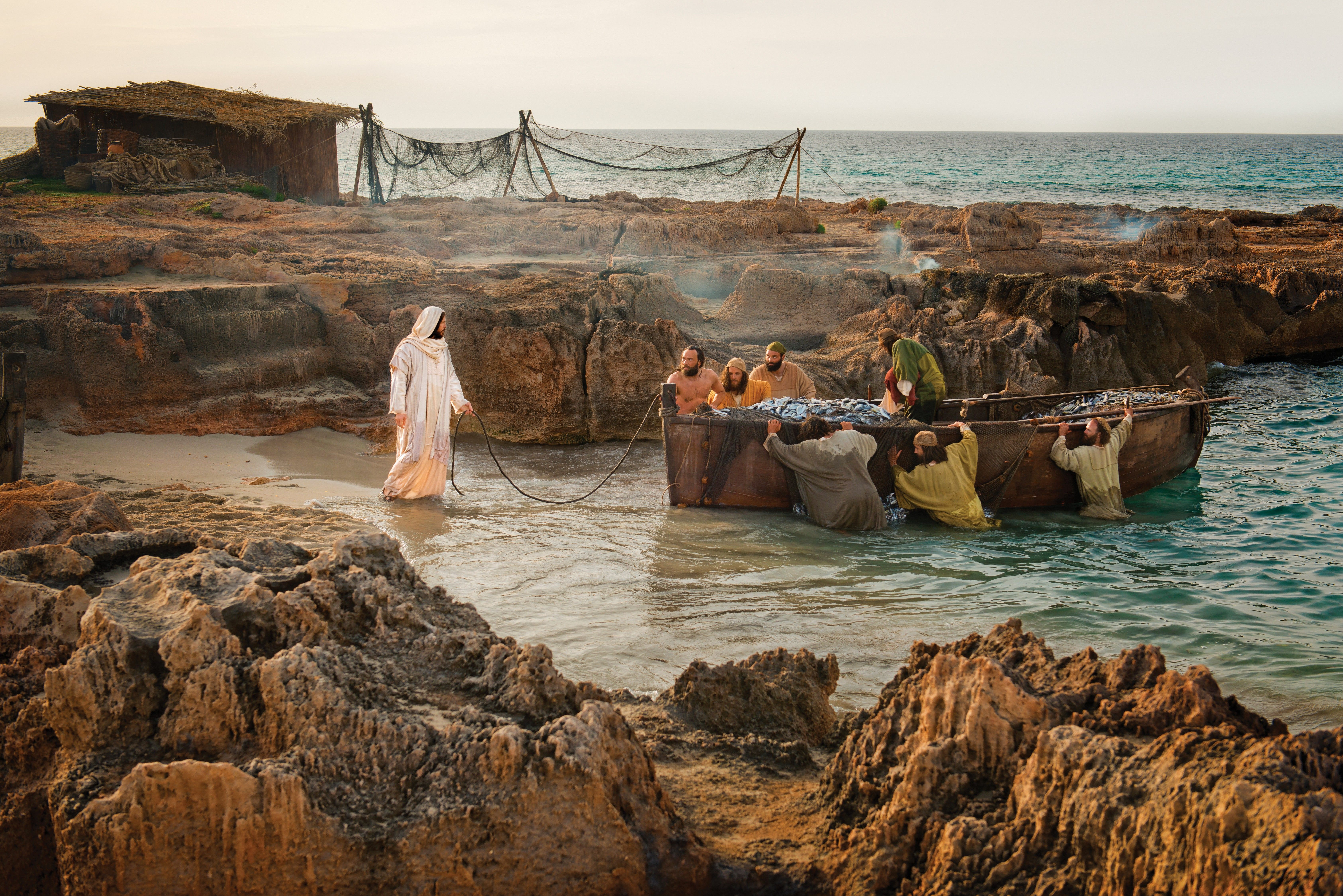 Christ standing in front of a boat that is being pushed by fishermen.