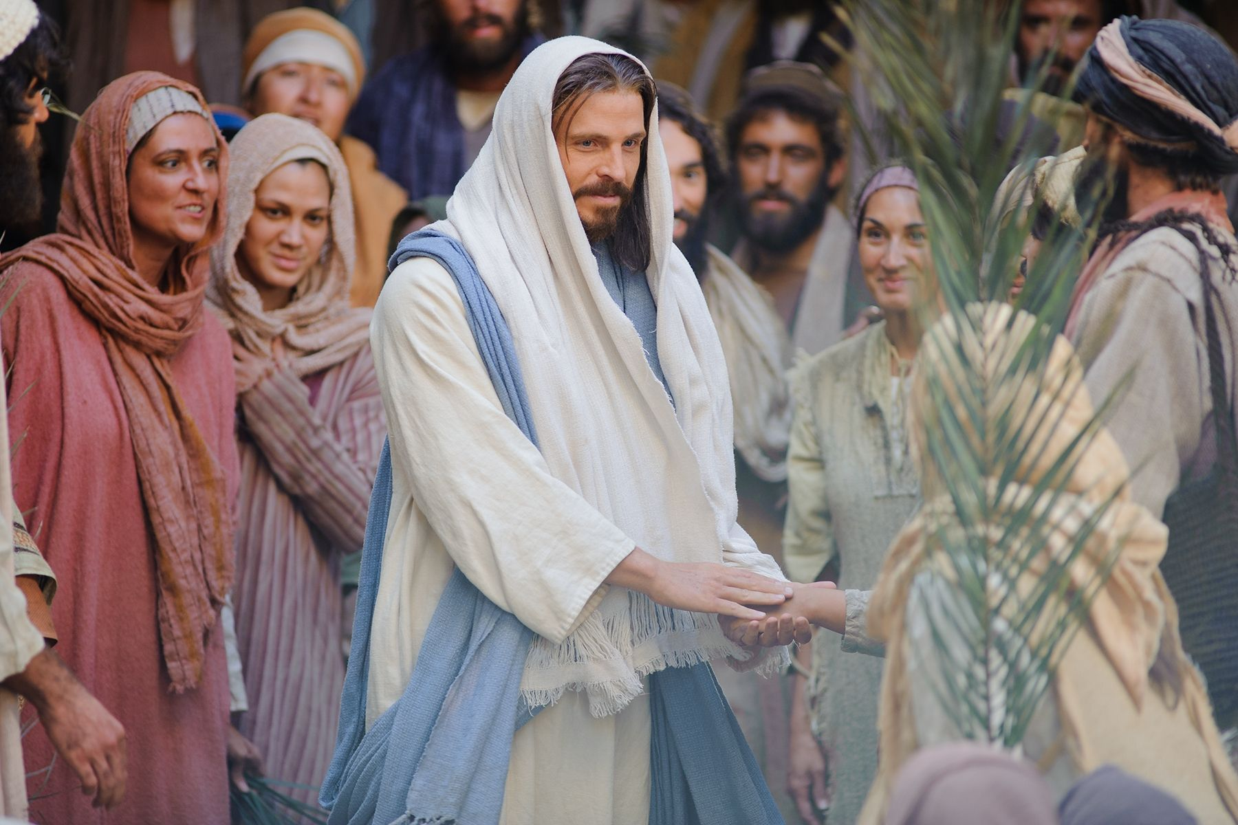 Followers of Christ wave palm leaves as Jesus enters Jerusalem.