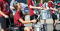 A young girl sits in a wheelchair while playing the drums. She is part of a parade