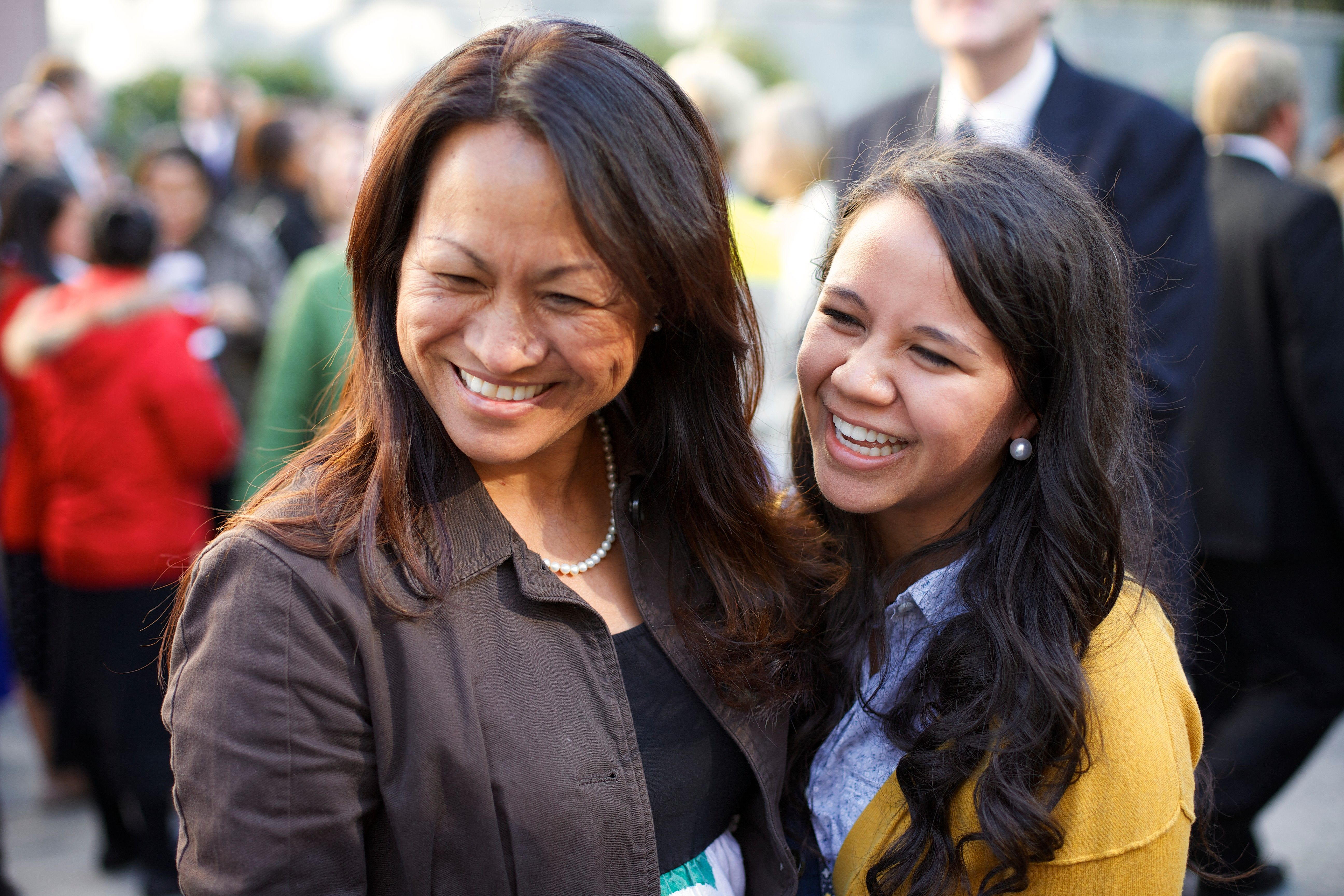 A woman standing and laughing with a young woman at general conference.