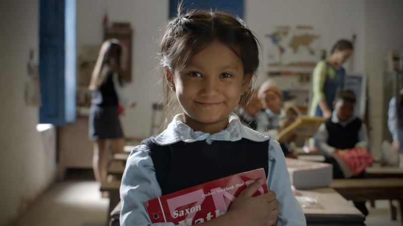 A little girl holds donated school books