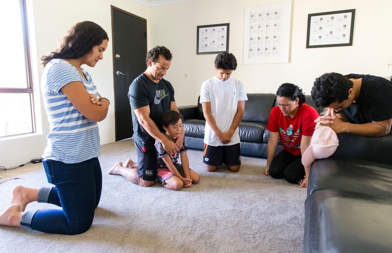 A couple and their children kneel together in family prayer