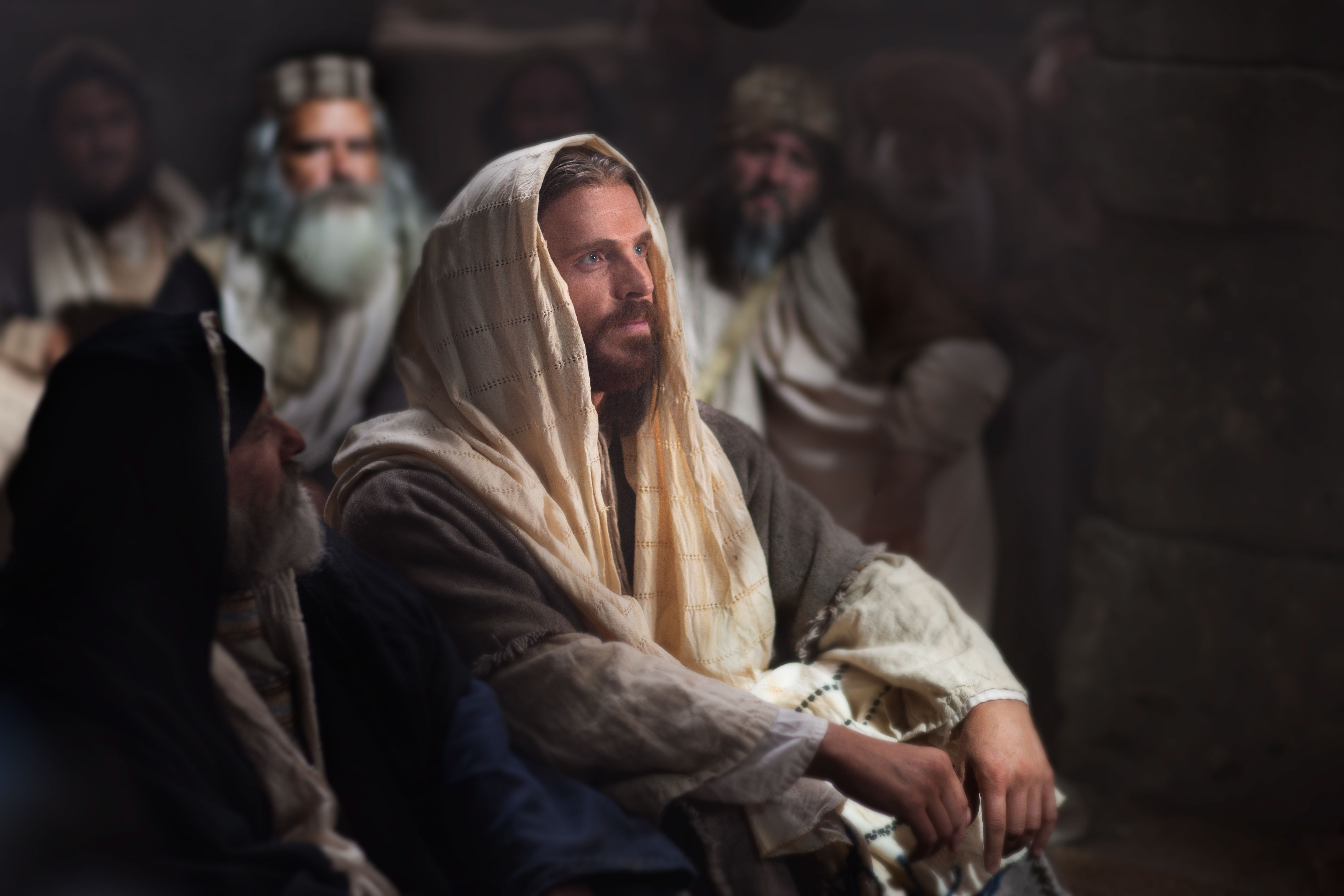 Jesus sits and listens as commotion breaks out after He declares He is the Messiah.