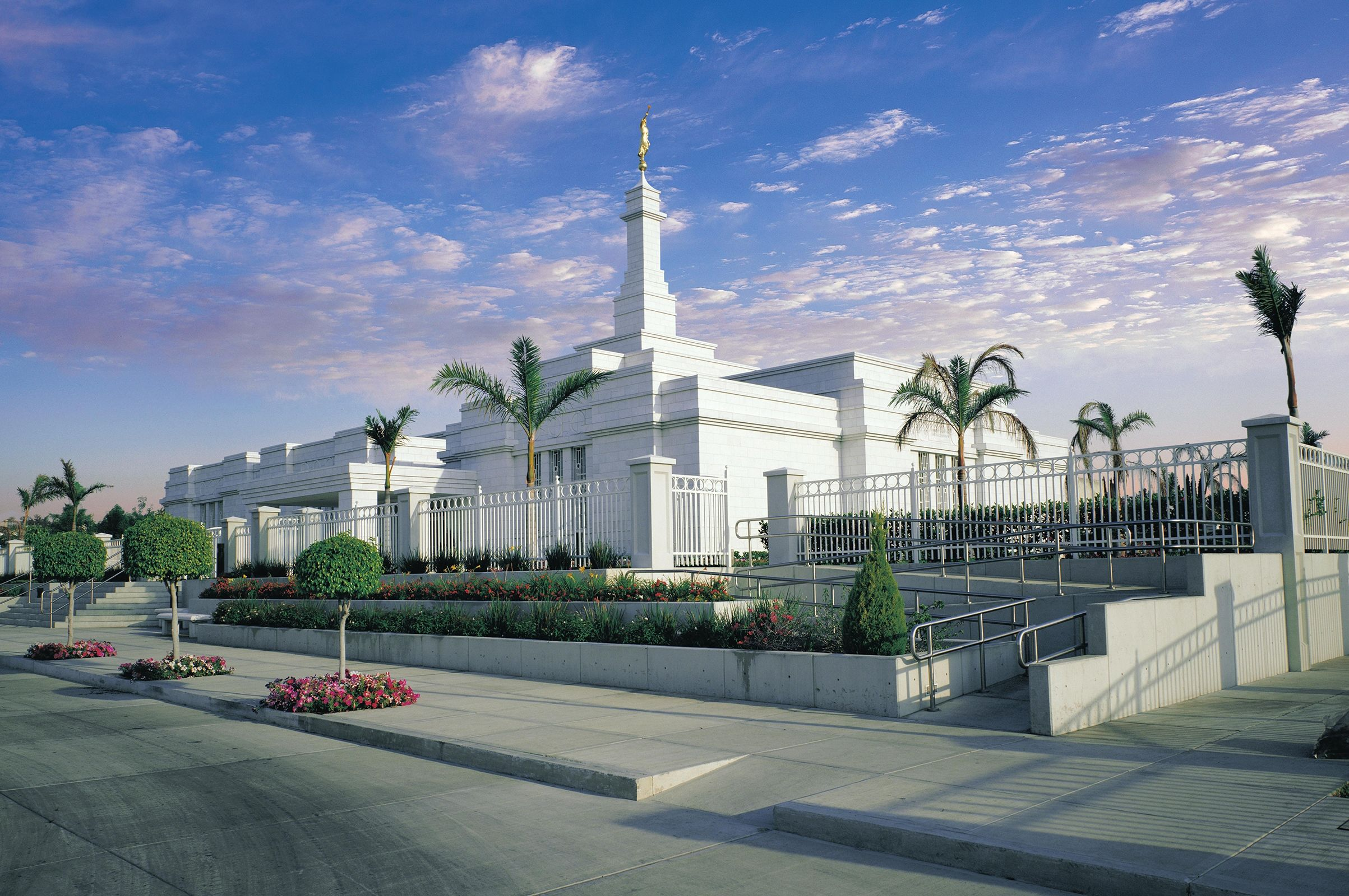 The Guadalajara Mexico Temple and grounds on a partly cloudy day.