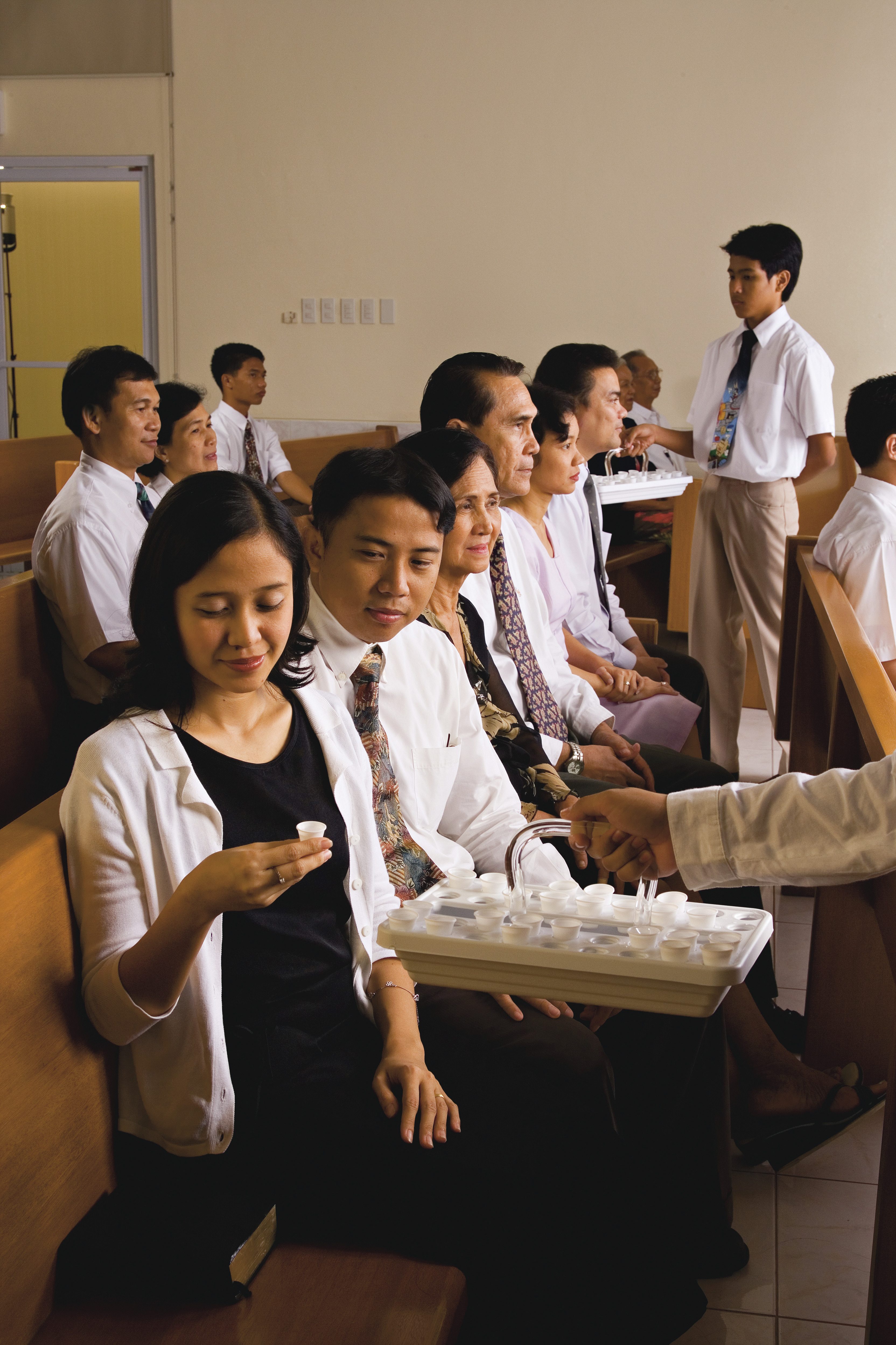 A woman takes the sacrament from a tray being passed to her.