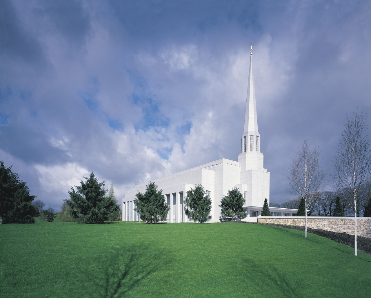 A view of the Preston England Temple from across its large green lawn on a partly cloudy day.