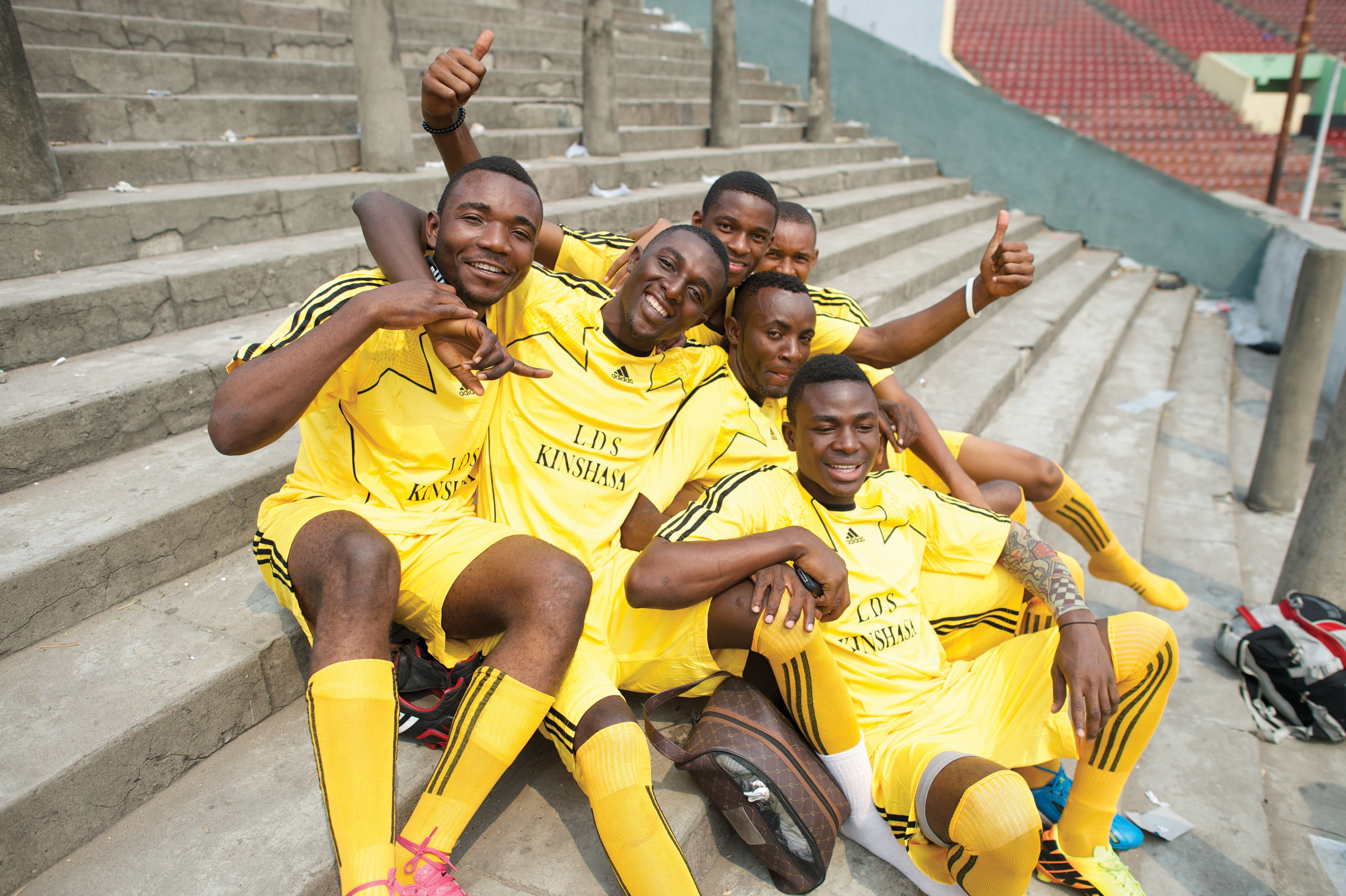 Soccer players from Africa sit in a group on stairs.