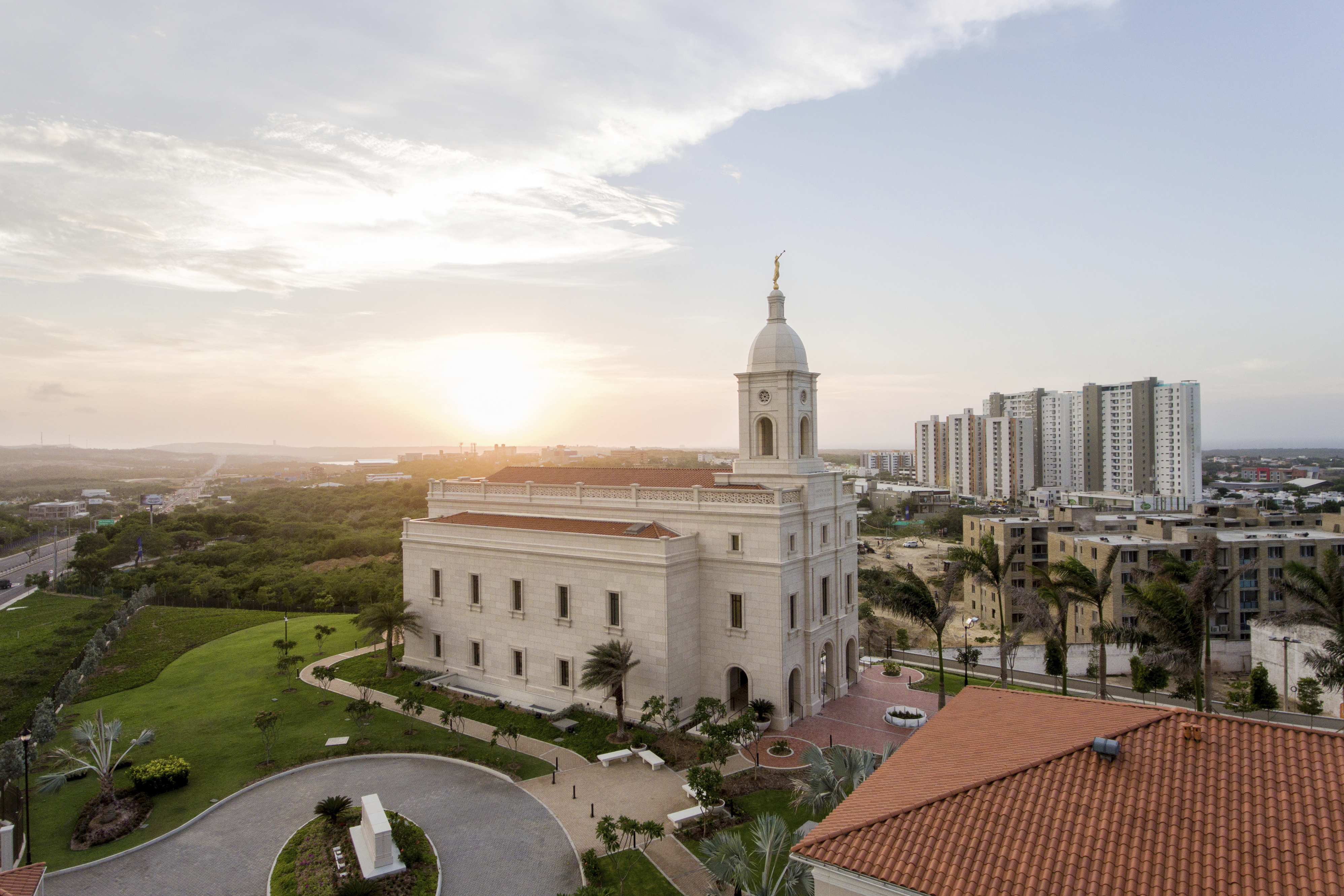 A side view of the entire Barranquilla Colombia Temple, surrounded by landscaping and city buildings.
